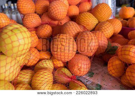 Fresh Oranges And Lemons In Plastic Mesh Sack For Sale At Farmers Market