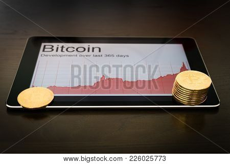 Blockchain Concept : Rise Of Bitcoin Price. Digital Tablet Showing Increasing Price Graph With Coins