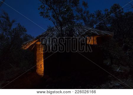 Primitive Adobe Hut With Thatched Roof Illuminated At Night By Moonlight And Interior Campfire Light