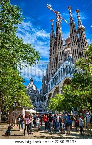 Barcelona, Spain - May 13, 2017: View Of The Gaudi Square With The Sagrada Familia Temple On The Bac