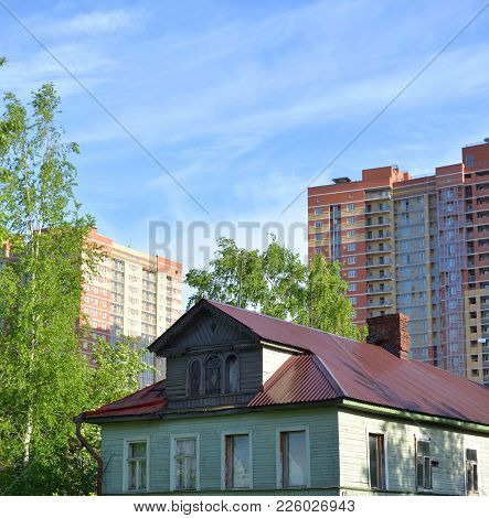 Old Wooden House And Modern Buildings Under Construction In The Village Of Ust-slavyanka On The Outs