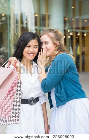 Closeup Portrait Of Young Beautiful Woman Looking At Camera And Whispering Secret To Smiling Asian G