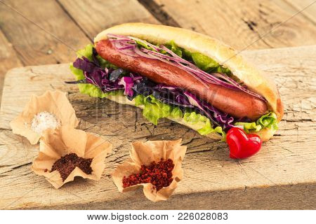 Hotdog With Sausage And Seasonings For Fast Food Lovers. Homemade Snack With Grilled Sausage And Oni