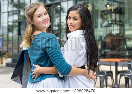 Closeup Portrait Of Two Smiling Young Beautiful Multiethnic Women Turning To Camera, Embracing And H