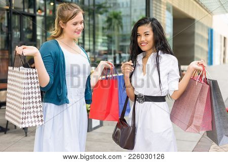 Closeup Portrait Of Two Young Beautiful Multiethnic Women Holding Paper-bags In City With Building I