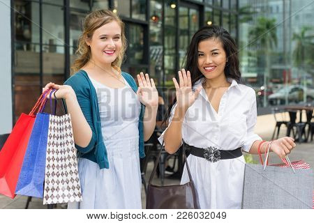 Closeup Portrait Of Two Young Beautiful Multiethnic Women Greeting Viewer And Holding Paper-bags In