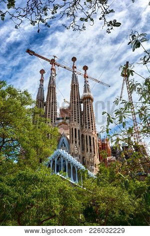 Barcelona, Spain - May 13, 2017: The Sagrada Familia Surrounded By Trees And A Beautiful Blue Sky, V