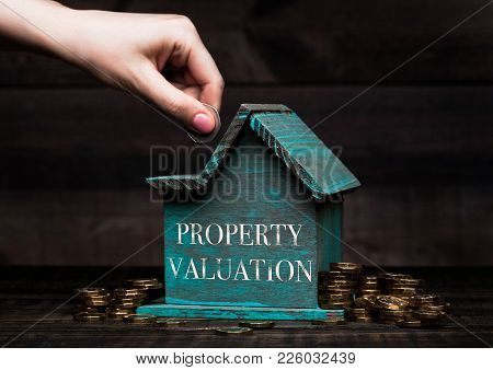 Wooden House Model With Coins Next To It And Hand Holding The Coin With Conceptual Text. Property Va