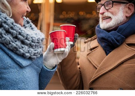 Close Up Of Arms Of Cheerful Old Man And Woman Celebrating Holiday Outdoor. They Are Drinking Mulled