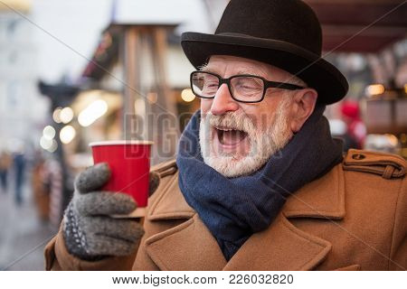 Portrait Of Excited Old Man Drinking Mulled Wine On Street. He Is Looking At Cup With Enjoyment And