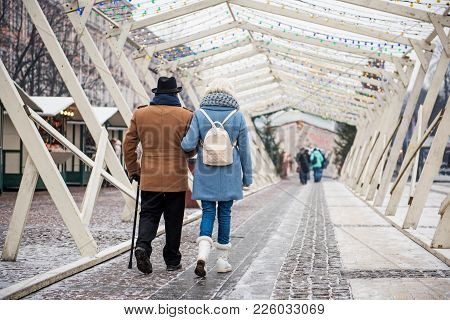 Back View Of Serene Old Man And Woman Walking Along Beautiful Street In The Winter. Copy Space