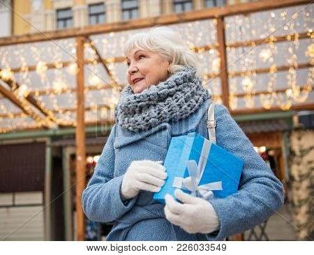 Excited Old Lady Is Standing On Street And Holding Gift Box. She Is Looking Aside With Anticipation