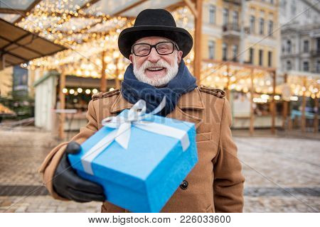 Portrait Of Joyful Mature Man Stretching Gift Box To Camera. He Is Standing On Street And Laughing.
