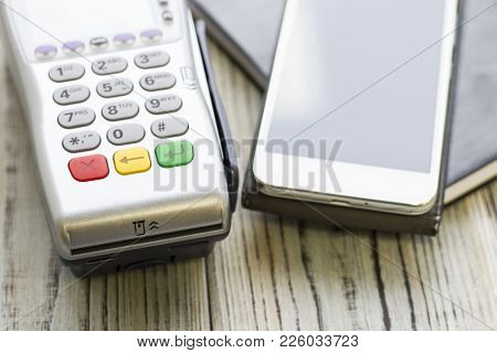 Modern Technology And People Concept - Pos Terminal And Telephone. Rough Bords Background. Closeup