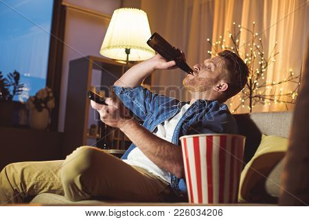 Side View Interested Unshaven Male Drinking Alcohol While Typing In Remote Controller In Apartment.