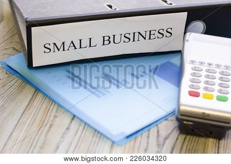Modern Technology And People Concept - Pos Terminal And Small Business Documents. Rough Bords Backgr