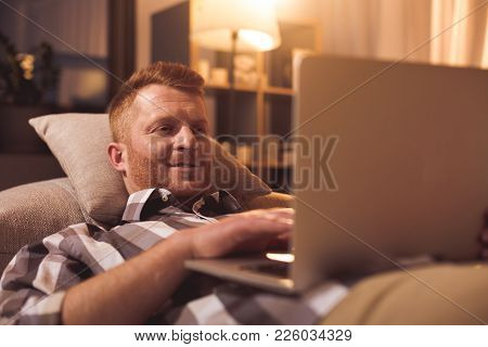 Portrait Of Cheerful Bearded Man Typing In Laptop While Lying On Sofa In Room. Relax Concept