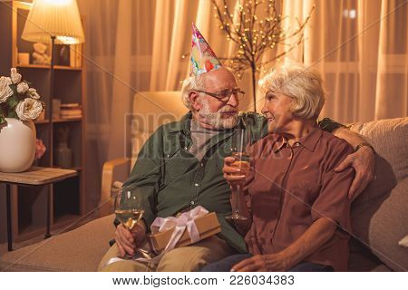 Glad Bearded Old Man Embracing Happy Woman While Drinking Champagne. They Sitting On Sofa. Birthday