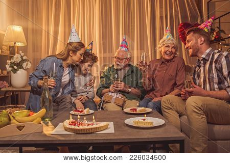 Outgoing Relatives Having Party. They Sitting On Sofa While Speaking With Each Other And Tasting Alc