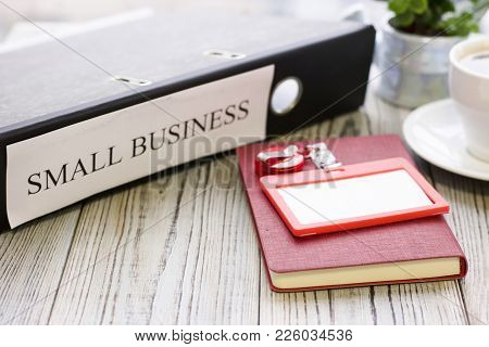 Planning Business Concept - Small Business Documents And A Notepad. Rough Bords Background. Closeup
