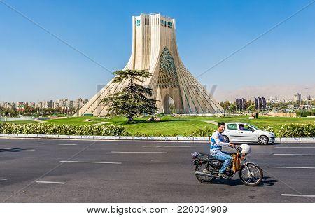 Tehran, Iran - October 15, 2016: Man Drives Scooter In Front Of Famous Teheran Landmark Azadi Tower