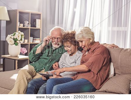 Cheerful Bearded Grandpa, Beaming Granny And Funny Boy Looking At Digital Device. They Locating On C