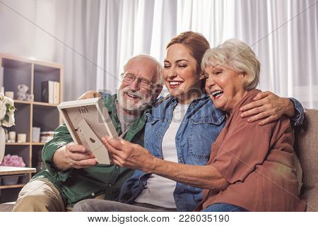 Portrait Of Laughing Grandparents And Smiling Young Woman Looking At Photo In Room. Remembrance Conc