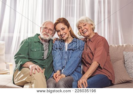 Portrait Of Cheerful Bearded Grandfather Sitting Near Glad Daughter And Outgoing Wife On Sofa. They