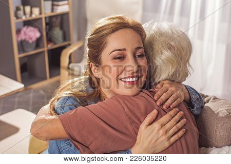 Cheerful Girl Embracing Mother. They Sitting In Living Room. Care Concept