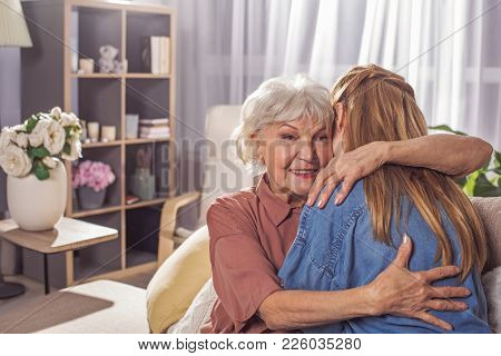 Cheerful Old Female Embracing Adult Daughter. She Turning Back To Camera. Care Concept