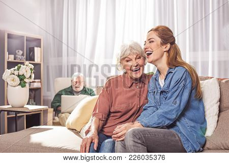 Portrait Of Cheerful Old Woman Laughing With Young Lady On Sofa. Beaming Bearded Grandfather Typing