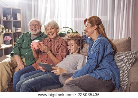 Cheerful Grandfather, Beaming Granny, Outgoing Boy And Glad Lady Relaxing On Sofa. Child Using Appli