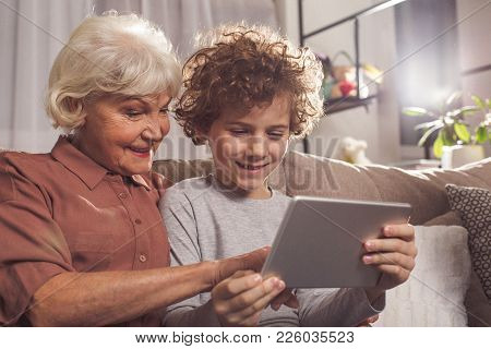Portrait Of Outgoing Grandmother And Glad Boy Looking At Digital Device In Apartment. Cheerfulness A