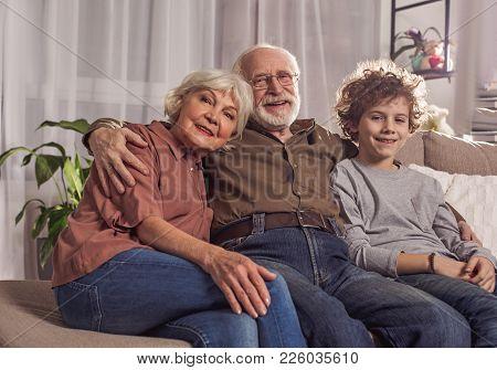 Portrait Of Cheerful Bearded Granddad Sitting Near Glad Grandmother And Cheerful Grandson On Sofa. H