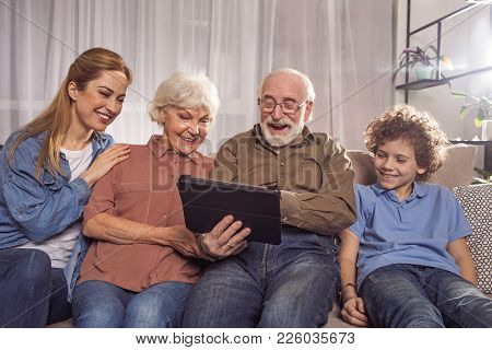 Portrait Of Cheerful Woman, Outgoing Grandparents And Beaming Boy Looking At Electronic Tablet While
