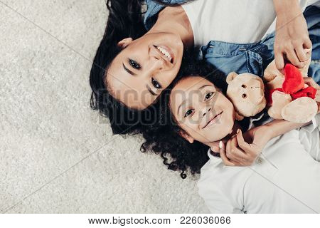 Top View Portrait Of Content Mother And Child Resting On Rug With Teddy Bear. Copy Space In Left Sid