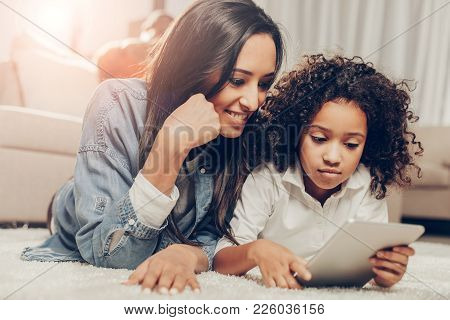 Happy Infancy Concept. Delighted Mom And Daughter Looking At Tab Screen While Resting On The Floor I