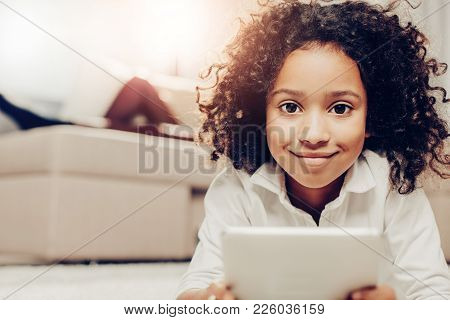 Portrait Of African Girl Spending Holidays At Home. She Is Looking At Camera While Holding Tab. Focu
