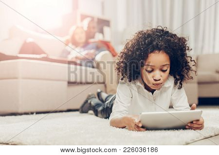Thoughtful Kid Looking At Tablet While Resting On Soft Tapis Inside. Focus On Girl. Parents On Backg