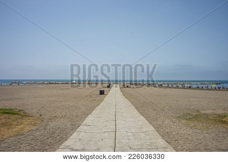 A Stone Pathway Leading To The Sea And Ocean At Malagueta Beach In Malaga, Spain, Europe On A Cloudy