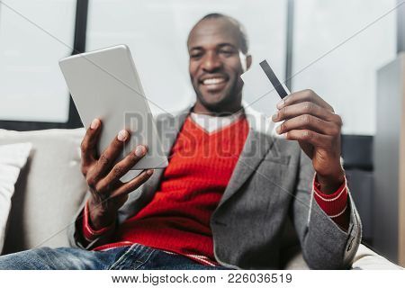 Low Angle Portrait Of Happy African Man Sitting On Couch And Holding Gadget And Payment Card. Focus