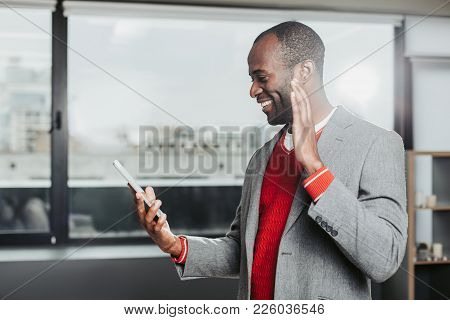 Profile Of Smiling African Man Looking At Tab And Waving. Association Concept