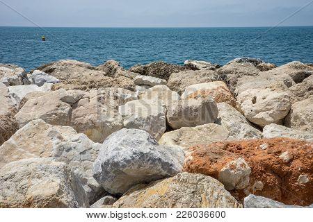 Rocks Against The Green Ocean At Malagueta Beach In Malaga, Spain, Europe