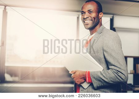 Waist Up Portrait Of Content Neat Man Holding Notebook In Hand While Standing Inside. Copy Space In