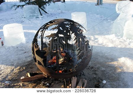 A Spherical Shaped Outdoor Fire Pit With Logs Burning In It.