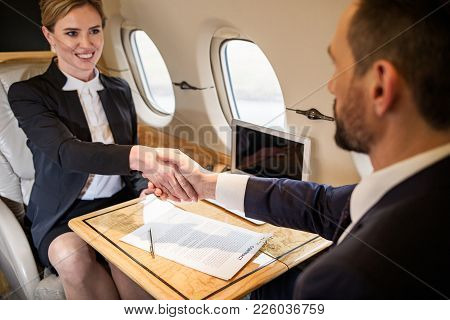 Contented Young Businesswoman Shaking Hands With Her Companion In Airplane, Contract Is Lying On Tra