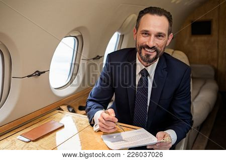 Portrait Of Glad Handsome Businessman In Airplane Cabin Sitting At Table With Some Documentation. He