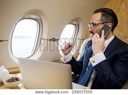 Success Concept. Glad Handsome Male Having Conversation By Cellphone While Sitting In Airplane Seat