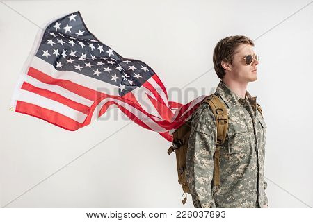 Severe Military Young Man Walking Somewhere With Serious Look. He Is Having Backpack On His Shoulder