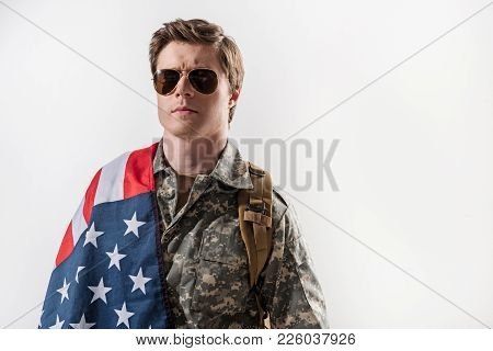 Waist Up Portrait Of Serious Military Guy Having Usa Flag On His Shoulder. He Is Standing With Backp